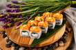 Lava maki sushi rolls with cream cheese at wooden tray decorated with lavender flowers and stones background.