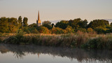 Beautiful dawn landscape image of River Thames at Lechlade-on-Thames in English Cotswolds countryside with church spire in background