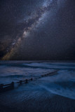 Vibrant Milky Way composite image over landscape of waves crashing onto beach - 225220795