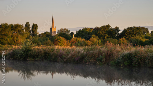 Sticker Beautiful dawn landscape image of River Thames at Lechlade-on-Thames in English Cotswolds countryside with church spire in background