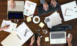 aerial view of a group of business people analyzes financial options on a brown office desk - 225221553