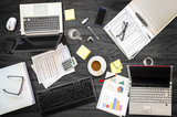 gray office desk at a business meeting with laptops, phones and financial papers, high angle view from above - 225226712