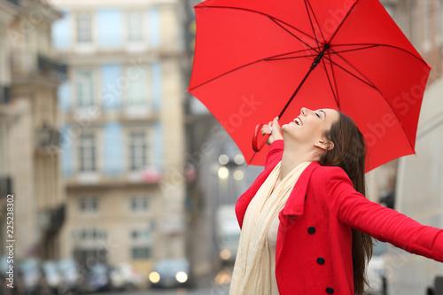 Spontaneous woman celebrating under the rain in winter