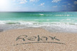 Holiday background or wallpaper with relax word handwritten on beach sand 