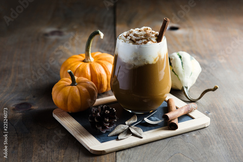 Wall mural Pumpkin latte with spices, coffee autumn of fall drink with pumpkins, Thanksgiving table, copy space, selective focus