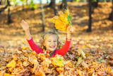 Happy little girl plays with autumn leaves in the park - 225249172