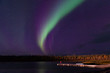 Lone photographer on dock photographing the aurora borealis