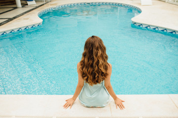 Woman sitting at the swimming pool, back view