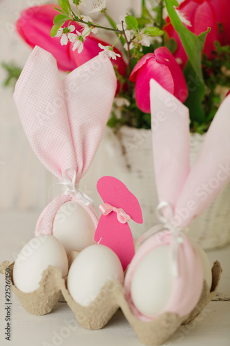 Happy easter. Decor of Easter eggs - napkins in the form of ears of Easter rabbits.