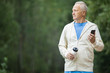 Senior active man in sportswear holding smartphone and bottle of water during morning workout in park