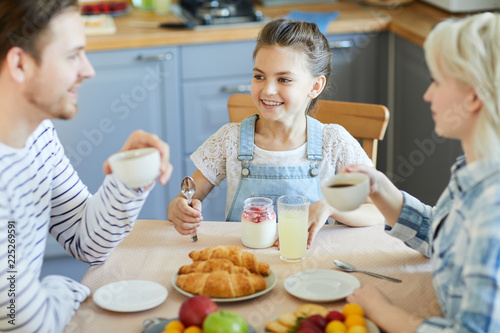 Happy little daughter looking at her dad while having breakfast by served table - 225269591
