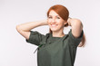 Fashion and people concept - beautiful young woman with red hair smiling over white background