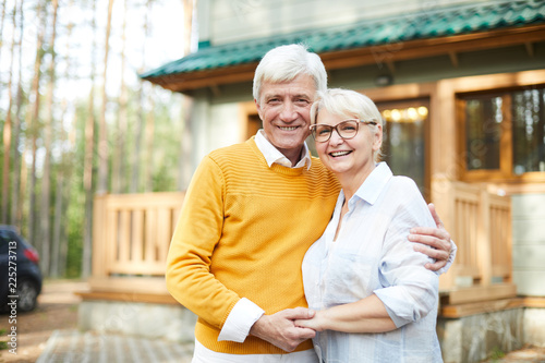 Forest house of grandparents: cheerful excited senior couple embracing each other and laughing while looking at camera and standing against cottage