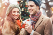 Leinwandbild Motiv Woman and man drinking mulled wine on Christmas Market in front of tree