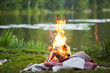 Burning campfire and plaid on green grass by river or lake in natural environment