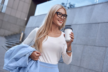 Young pretty spectacled businesswoman smiling and walking near business building with coffe