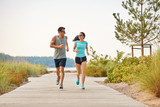 fitness, sport and lifestyle concept - happy couple in sports clothes and sunglasses running along summer beach path - 225292569