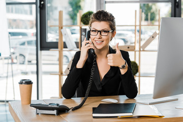 smiling attractive businesswoman talking by stationary telephone in office and showing thumb up
