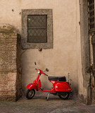 Red scooter parked in a side street in Siena, Tuscany