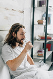 side view of young bearded man with long hair having headache and taking pill with glass of water in bedroom at home - 225310103