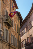 Palio flags waving from a balcony in Siena, Tuscany