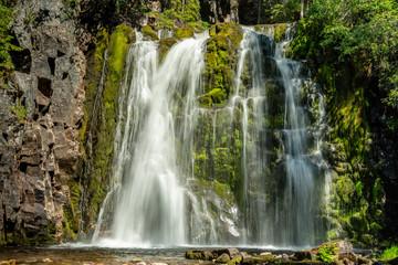 Beautiful waterfall flowing down a green rock wall