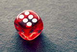 Close up picture of six on a red dice, selective focus, color toning applied.