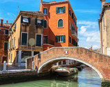 Venetian canal between old buildings and small brick footbridge on foreground, Italy. - 225331979