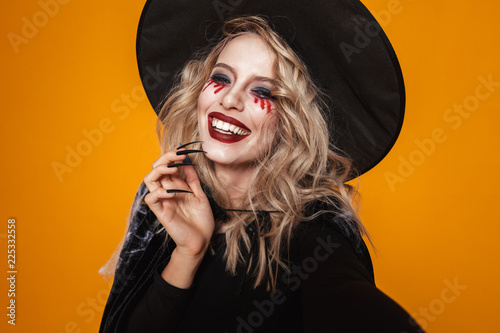 Leinwandbild Motiv Portrait of woman witch in hat looking camera and smiling