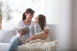 Happy mother reading book to smiling daughter while relaxing at home