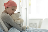 Weak girl with cancer wearing pink headscarf and hugging teddy bear - 225333132