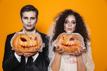 Photo of scary zombie couple bridegroom and bride wearing outfit and halloween makeup holding carved pumpkin, isolated over yellow background