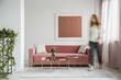 Blurred woman walking in a feminine living room interior with a sofa, coffee table and painting