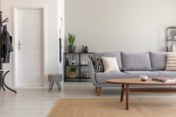 Wooden table on carpet in front of grey sofa in minimal living room interior with door. Real photo