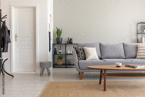 Wooden table on carpet in front of grey sofa in minimal living room interior with door. Real photo © Photographee.eu