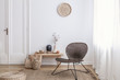 Modern armchair and pouf on brown carpet in white apartment interior with door. Real photo