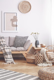 Patterned blanket on wooden couch in white living room interior with poster and baskets. Real photo - 225333909
