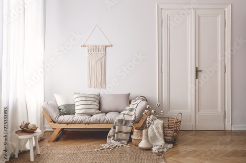 Leinwandbild Motiv Pillows and blanket on wooden sofa in white loft interior with door and table on carpet. Real photo