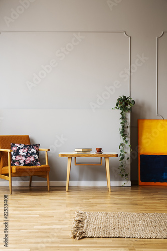 Wooden table between armchair and painting in grey apartment interior with plant and rug. Real photo - 225334108