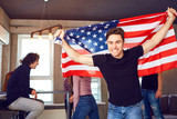 Guy with a beautiful smile with the flag of america indoors. Independence Day of the USA.