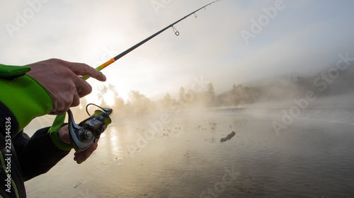 Foto Murales Man fishing in river with fly rod during summer morning.