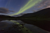 Aurora in the night sky cut the mountains, reflected in the water. Yamal. Russia - 225356392