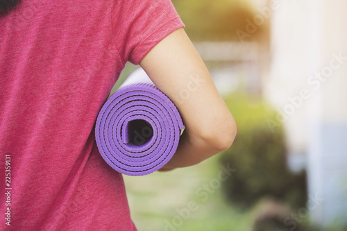 Fototapeta Young woman holding a yoga mat in exercise class for a sport and healthy concept