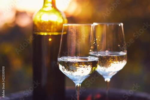 Two glasses of white wine at sunset - 225359310