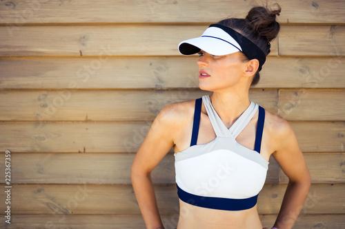 pasuje kobieta jogger patrząc na bok na drewnianej ścianie