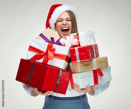Foto Murales Happy woman wearing santa hat holding pile of gifts.