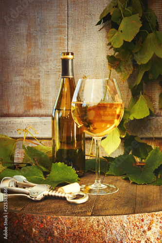 Bottle of white wine with glass on barrel