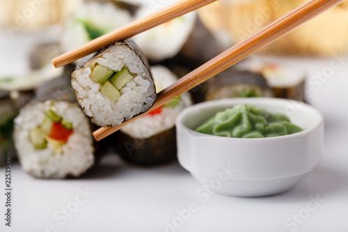 Female hand holding wooden sticks Philadelphia roll with salmon