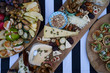 Snacks for beer with different food, close-up. Salty and cheese bar of several kinds of cheese, grapes, olives, nuts, fruits  decorated on table. Holiday party outdoors, picnic