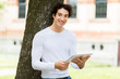 Young guy using a digital tablet lying against a tree in the park and enjoying the freedom of rhe wireless internet connection